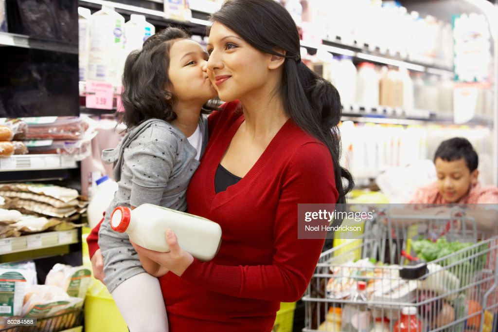 Indian mother grocery shopping with children : Stock Photo