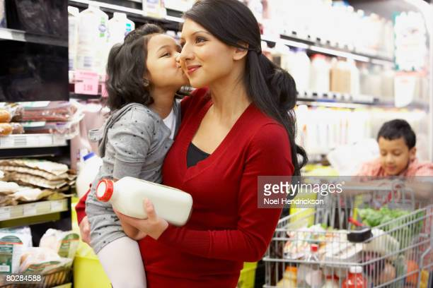 indian mother grocery shopping with children - indian girl kissing stock photos and pictures