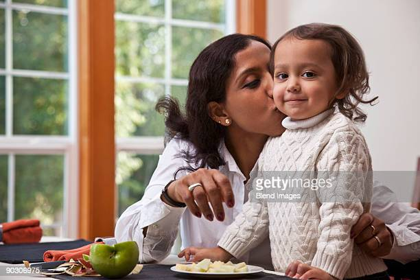 Indian mother kissing daughter