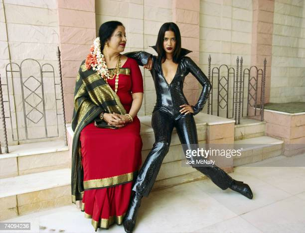 Indian mother poses with model daughter in contrasting outfits the mother in traditional Indian garments while the daughter wears a black sparkling...