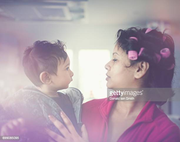 indian mother wearing curlers holding son - aunt stock pictures, royalty-free photos & images