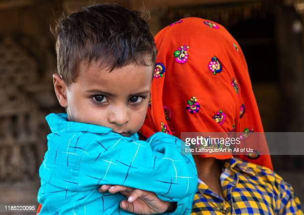 Indian mother with face covered by a sari with her son Rajasthan Abhaneri India on July 14 2019 in Abhaneri India