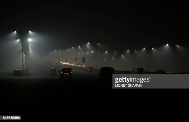 Indian motorists drive amid fog in New Delhi on December 26 2017 / AFP PHOTO / MONEY SHARMA
