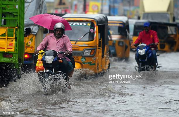 Indian motorists drive through a flooded street during heavy rains in Chennai on May 18 2016 While northern and central India is reeling under high...