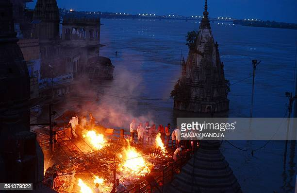 TOPSHOT Indian mourners perform a cremation on the roof of a building overlooking The Manikarnika Ghat in Varanasi on August 23 2016 India's holy...