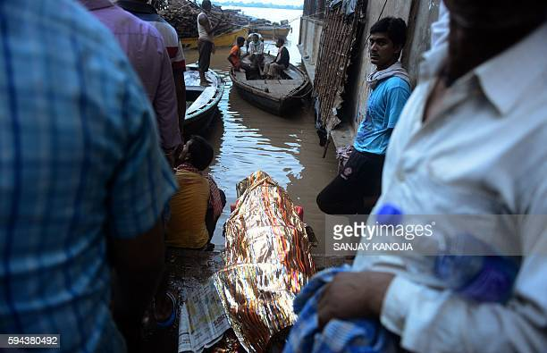Indian mourners wait for a boat to transport the body of a relative through floodwaters to the cremation site of The Manikarnika Ghat in Varanasi on...