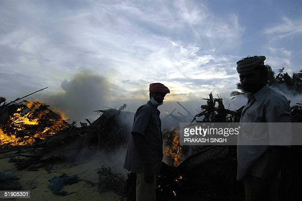 Indian municipal workers burn the debris of what once was a village as the sun sets at Velankanni beach some 365 km south of Madras 31 December 2004...