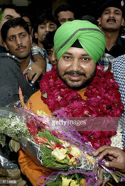Indian musician Daler Mehndi holds a bouquet of flowers as he leaves the arrivals area of Lahore International Airport 19 March 2004 Mehndi has...