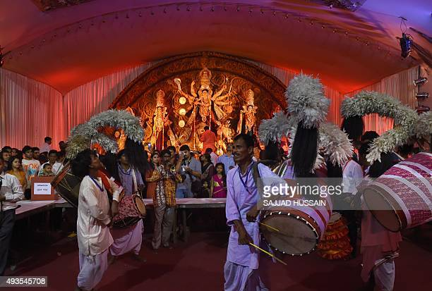 Indian musicians play drums as a Hindu priest offers evening prayer in front of an idol of the Goddess Durga in New Delhi on late October 202015 The...