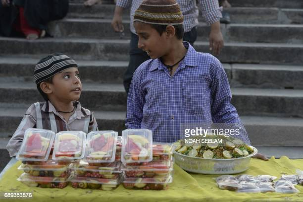Indian Muslim boys wait for devotees to buy food before breaking their fast on the first day of the Islamic holy month of Ramadan at Mecca Masjid in...