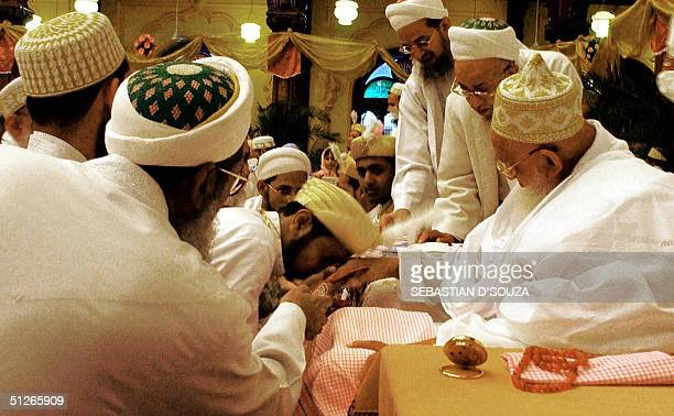 Indian Muslim bridegrooms of the Dawoodi Bohra sect wait their turn to kiss the hand of his holiness Dr Syedna Mohammed Burhanuddin at the collective...