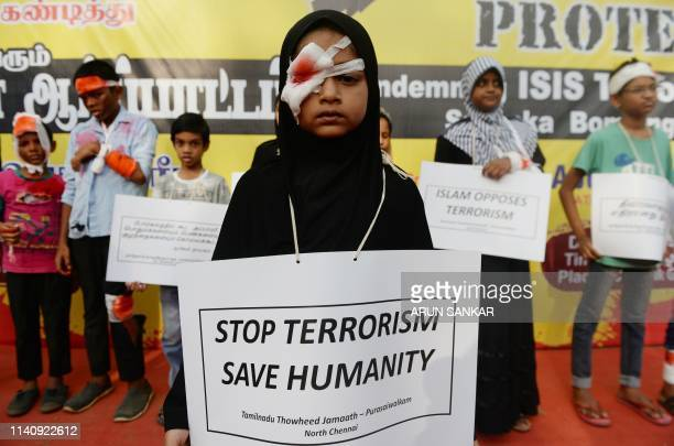Indian Muslim children, holding placards and dressed as if they were injured, take part in a demonstration organized by the Tamilnadu Thawheedh...