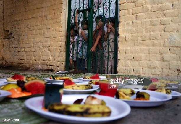 Indian Muslim children look at food being prepared from behind a fence while waiting for food handouts before breaking their fast at sunset during...