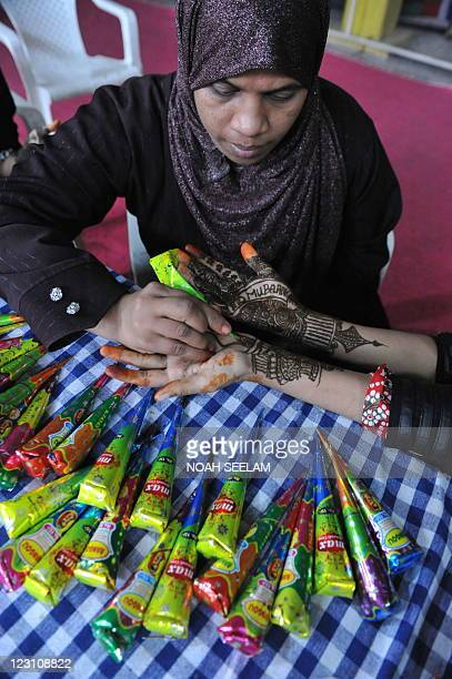 Indian Muslim designer Salman Khursheed applies mehendi on the hands of a customer during 'Chand Raat' or 'Night of the Moon' in Hyderabad on August...