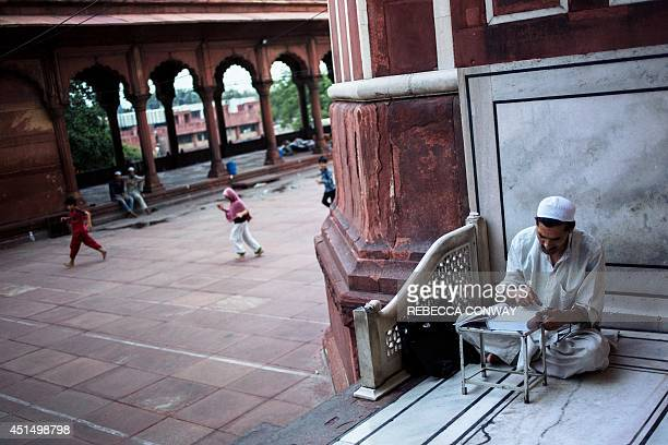 Indian Muslim devotee Nazir Ahmed Wani who is visiting India's capital from Srinagar reads the Quran after dawn prayers inside the Jama Masjid on the...