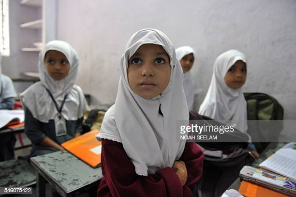 Indian Muslim girls students listen to a teacher in a class at MadinatulUloom school in Hyderabad on July 11 on World Population Day Indias...