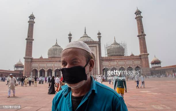 Indian Muslim man wearing a protective mask leaves after attending congregational Friday prayers at the historic Jama Masjid amid the government...