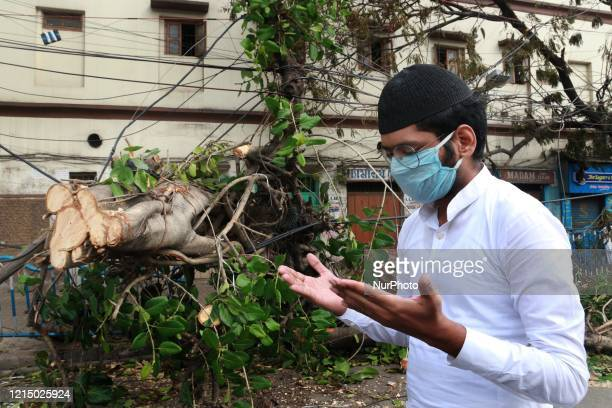 Indian Muslim offers a special prayer on Road in the brackdrop a tree branch fallen on a road after Cyclone Amphan hit the region in Kolkata during...