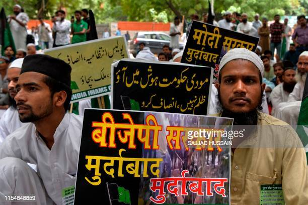 Indian Muslim social activists hold placards as they take part in a rally called 'Stop atrocities Save country' against the string of violent...