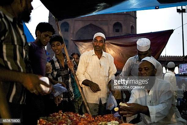 Indian Muslim vendors arrange fruits to sell to break the fast at Iftar on Chand Raat the last evening of the holy Islamic month of Ramadan outside...