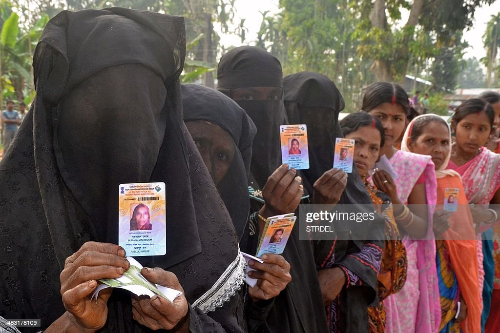 Indian Muslim voters pose with identification as they wait in line to vote outside a polling station in Koliabor, in Assam state's Nagoan district some 180 kms east of Guwahati, on April 7, 2014. Indians have begun voting in the world's biggest election which is set to sweep the Hindu nationalist opposition to power at a time of low growth, anger about corruption and warnings about religious unrest. India's 814-million-strong electorate are forecast to inflict a heavy defeat on the ruling Congress party, in power for 10 years and led by India's famous Gandhi dynasty.