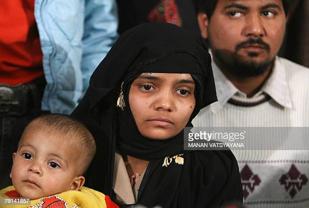 Indian Muslim woman Bilkis Yakub Rasool holds her son Mohammad as she addresses a media conference in New Delhi 21 January 2008 as her husband Yakub...