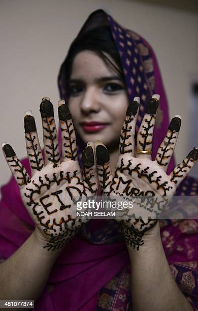 Indian Muslim woman Feroze Jahan Begum poses showing her hands decorated with mehendi designed with Eid Mubarak wishes during 'Chand Raat' or 'Night...