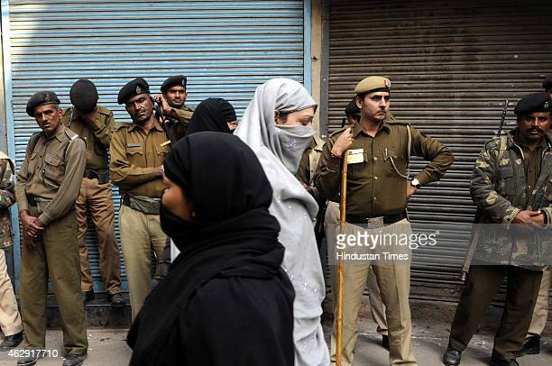 Indian Muslim women are passing by a group of police men at old Delhi area to cast their vote at nearest polling booth during the Delhi Assembly...