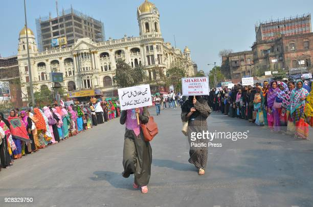 Indian Muslim women hold placards and take part in a silent protest rally to demand a repeal of the 'triple talaq' or instant divorce bill
