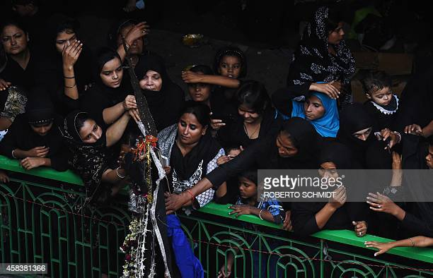 Indian Muslim women reach over to touch a palm shaped amulet which represents the five holy persons of prophet Muhammad's family at the end of a...