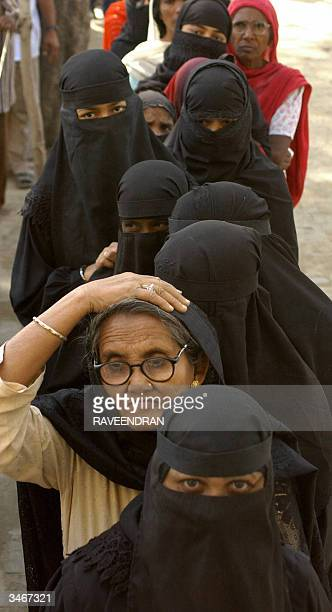 Indian Muslim women wait in line to cast their votes in Indian's general election outside a polling station in Rae Bareli some130 kms south of...