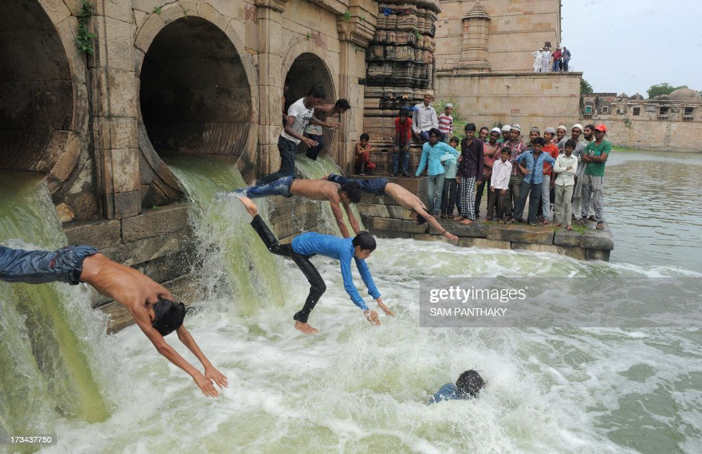 Indian Muslim youth dive as flood waters enter the tank of the 600 year old Sarkhej Roza architectural complex, which has been dry for the last seven years, in Ahmedabad on July 14, 2013. The Sarkhej Roza is maintained by the Archeological Survey of India and this tomb and mosque of a Sufi saint are known in this region as 'Ganj Bakhsh'. AFP PHOTO / Sam PANTHAKY