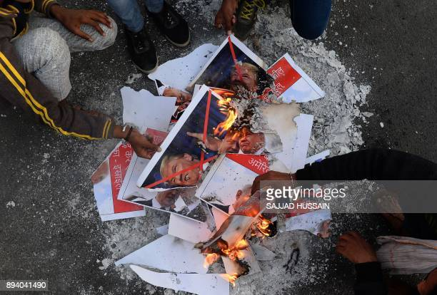 Indian Muslims burn pictures of US President Donald Trump and Israeli Prime Minister Benjamin Netanyahu during a rally in New Delhi on December 17...