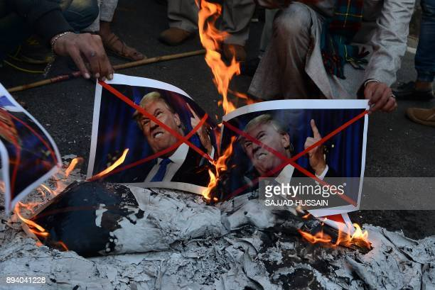 Indian Muslims burn pictures of US President Donald Trump during a rally in New Delhi on December 17 following US President Donald Trump's decision...
