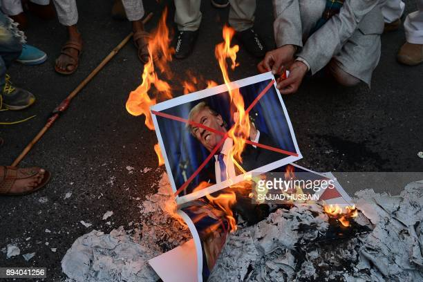 TOPSHOT Indian Muslims burn pictures of US President Donald Trump during a rally in New Delhi on December 17 following US President Donald Trump's...