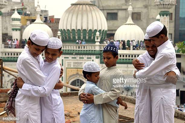 TOPSHOT Indian Muslims embrace after offering Eid prayers on the occasion of the Eid alFitr festival which marks the end of the holy month of Ramadan...