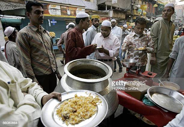 Indian Muslims have food following prayers on the occasion of the Eidal Fitr festival at the Jama Masjid mosque in New Delhi 04 November 2005 Muslims...