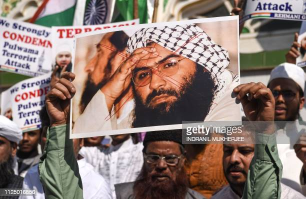 Indian Muslims hold a scratched photo of JaisheMohammad group chief Maulana Masood Azhar as they shout slogans against Pakistan during a protest in...