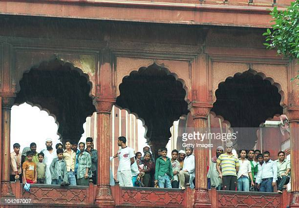 Indian Muslims peer out of the Jama Masjid mosque after gunmen attacked foreign tourists on September 19 2010 in New Delhi India According to Police...