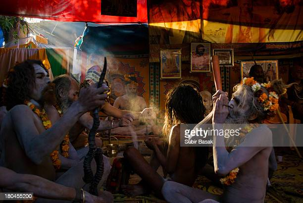 CONTENT] Indian Naga sadhus smoking at their tent in Haridwar 15 March 2010 during the Kumbh Mela the largest Hindu gathering in the world Hindus...