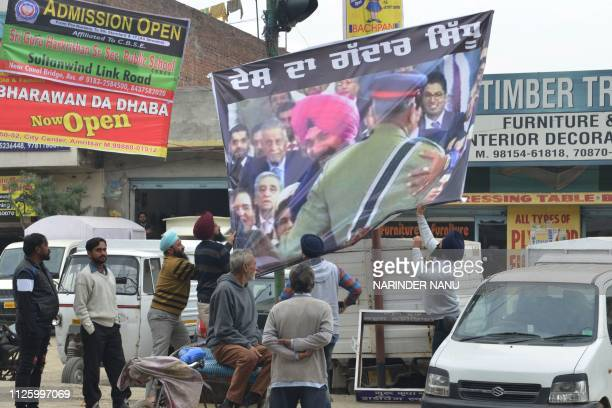 Indian National Congress party activist remove a banner with a picture of Punjab Cabinet minister Navjot Singh Sidhu embracing Pakistani Army Chief...