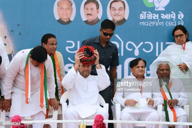 Indian National Congress party Vice President Rahul Gandhi removes a traditional turban at Khatraj village some 35 kms from Ahmedabad on October 9...