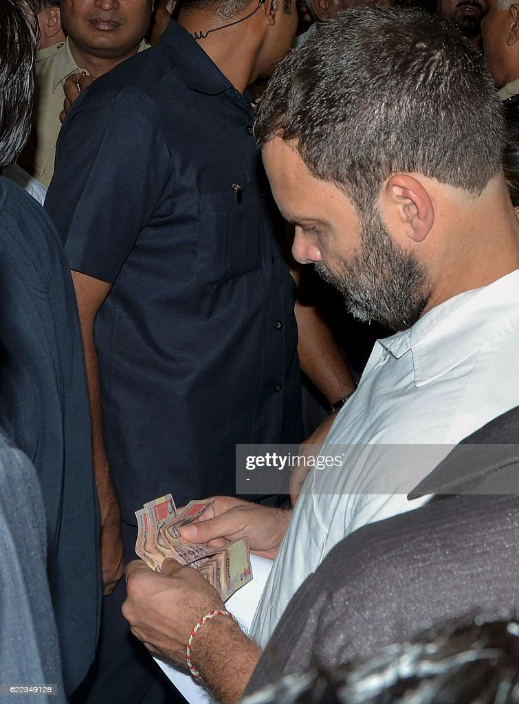 Indian National Congress vice-president Rahul Gandhi carries old denomination 1000 rupee notes at a bank as he arrives to exchange them in New Delhi on November 11, 2016. Long queues formed outside banks in India as people crowded into deposit and withdraw money after the two largest denomination notes were taken out of circulation. / AFP / -