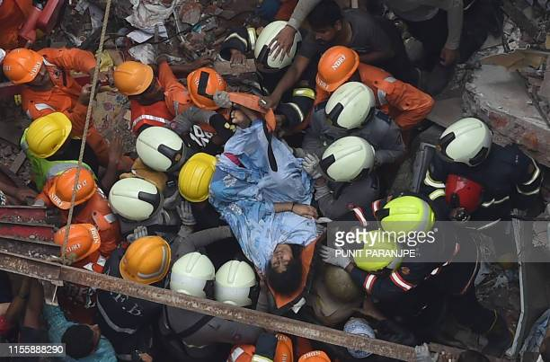 Indian National Disaster Response Force and Indian fire brigade personnel rescue a survivor after a building collapsed in Mumbai on July 16, 2019. -...
