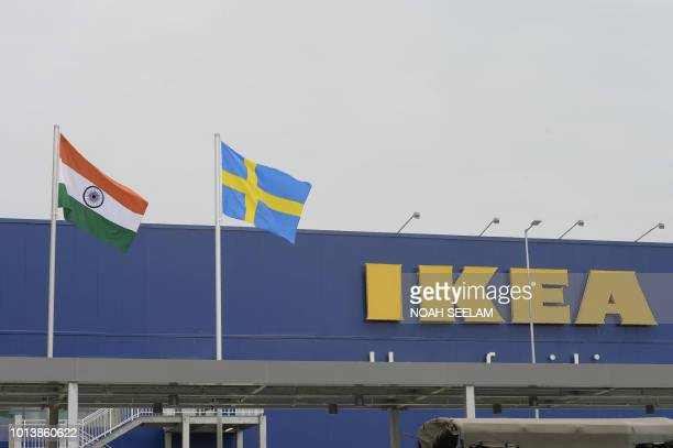 Indian National flag and Swedish flag are pictured at the new IKEA store in Hyderabad on August 9 2018 Curious customers lay on beds and nestled into...