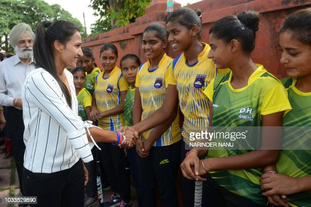 Indian national hockey captain Rani Rampal greets youth field hockey players during her visit to the Khalsa Hockey Academy in Amritsar on September...