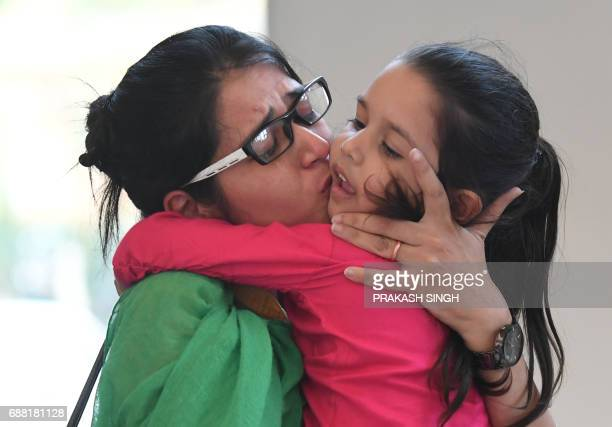 Indian national Uzma Ahmed kisses her daughter after her return from Pakistan at the Foreign Ministry in New Delhi on May 25 2017 An Indian woman who...