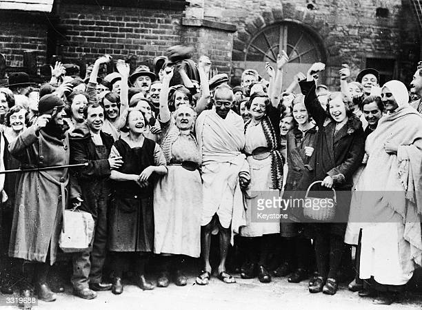 Indian nationalist leader Mahatma Gandhi is greeted by a crowd of female textile workers during a visit to Darwen Lancashire