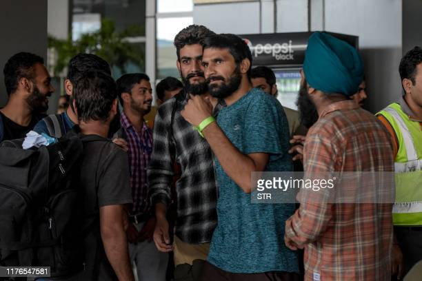 Indian nationals arrive at Indira Gandhi International airport in New Delhi on October 18 after being deported from Mexico as they tried to enter the...