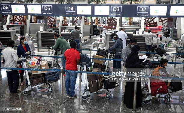 Indian nationals residing in Oman, wearing face masks due to the COVID-19 coronavirus pandemic, queue with their luggage at the check-in counter at a...
